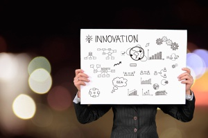 Innovation, person holding a white board with picture representing innovation.